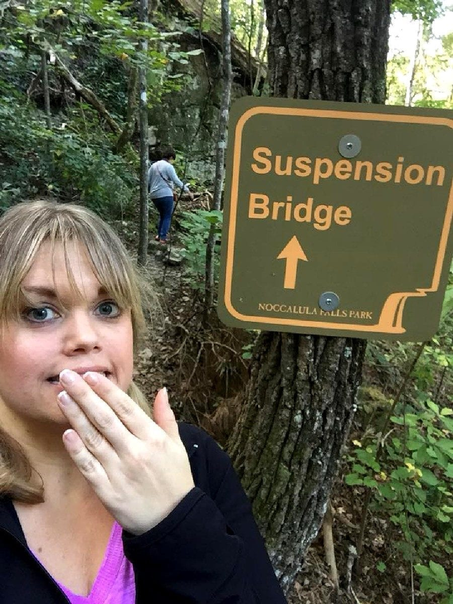 Conference attendee beside directional sign for Suspension Bridge.