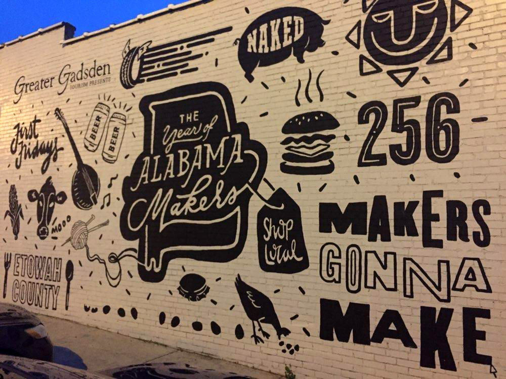 Mural highlighting downtown businesses near Pitman Theater.