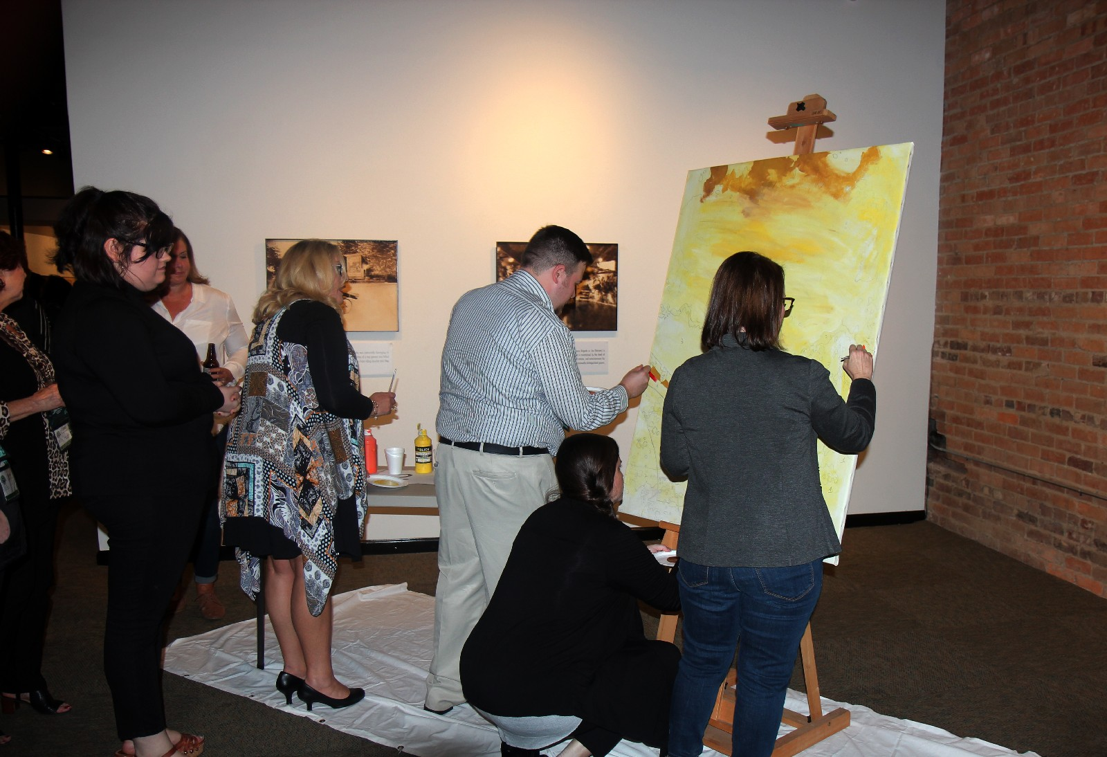 Conference attendees participating in a paint-by-numbers project during reception at Gadsden Museum of Art.