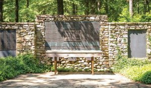 A three-sided stone memorial holds bronze plates honoring the dedication and work of deceased Extension employees